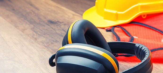 Ear protection hard had construction and reflective shirt placed on the wooden floor represents the concept of keeping the quality of hearing